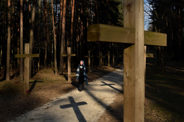 A woman walks past crosses on April 4, 2019 outside Minsk at the Kuropaty unofficial activist erected wooden crosses memorial known as a site where the Soviet secret police shot and buried thousands victims of the Soviet-era political repressions in the 1930s and 40s, as authorities demolished today some 70 large crosses erected in the area after a crowdfunded campaign were razed. An activist said police cordoned off the area from activists and journalists, while construction workers put up a fence. He and 14 other activists and opposition politicians were later detained at the site, police told Belarusian media. (Photo by Sergei Gapon/AFP Photo)