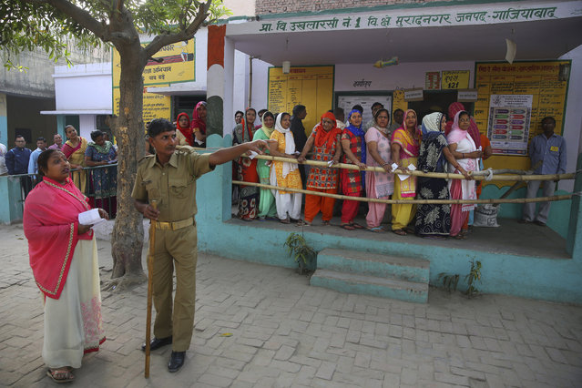 A policeman guides a woman to her respective polling booth as others wait in a queue to cast their votes for the first phase of general elections, near Ghaziabad, India  Thursday, April 11, 2019. Voters in 18 Indian states and two Union Territories began casting ballots on Thursday, the first day of a seven-phase election staggered over six weeks in the country of 1.3 billion people. (Photo by Manish Swarup/AP Photo)