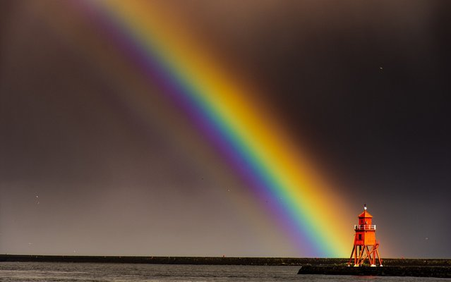 Photographer John Fatkin captured these jaw-dropping images of a rainbow and ferry on the River Tyne, England, with the iconic red-painted Herd Groyne Lighthouse. (Photo by Tom Fatkin/Cover Images)