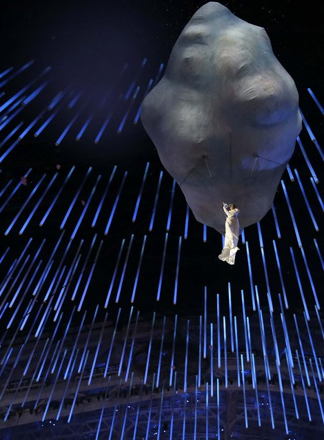 An artist is suspended as she performs during the closing ceremony. (Photo by Darron Cummings/Associated Press)