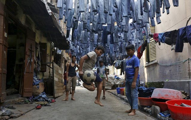 Mohammad Afroze, 15, plays soccer in an alley as used pairs of jeans are hung to dry before they are sold in a second-hand clothes market in Kolkata, India, March 10, 2016. Afroze said he loves Kolkata because he was born in the city and people love to play soccer. (Photo by Rupak De Chowdhuri/Reuters)