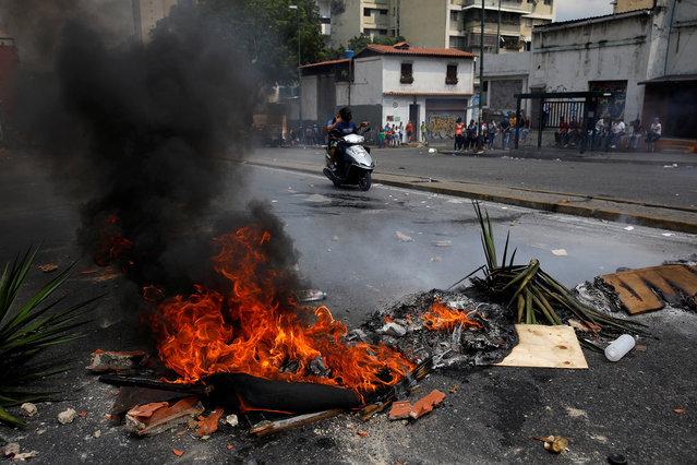 A fire barricade burns at a protest against the government of Venezuelan President Nicolas Maduro in Caracas, Venezuela March 31, 2019. (Photo by Carlos Garcia Rawlins/Reuters)