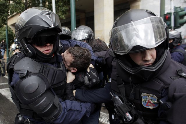 Riot policemen detain a protester during a demonstrator against austerity measures in Athens, on Friday March 6, 2014. Riot police have used tear gas and pepper spray during scuffles with union members protesting austerity measures, during a ban on demonstrations in parts of central Athens due to a visit by German President Joachim Gauck. Scuffles broke out when a group of several dozen demonstrators attempted to break through a police cordon on a major avenue in an effort to march to the Finance Ministry. (Photo by Kostas Tsironis/AP Photo)