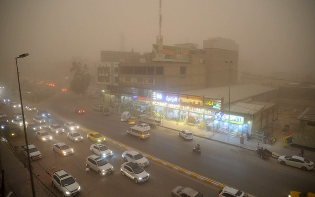 Cars drive through a street in Iraq's central city of Najaf during a sand storm on April 29, 2019. (Photo by Haidar Hamdani/AFP Photo)