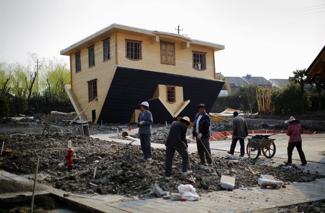 Labourers work at an upside-down house under construction at Fengjing Ancient Town, Jinshan District, south of Shanghai, March 17, 2014. (Photo by Carlos Barria/Reuters)