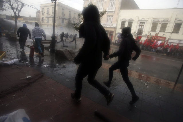 Masked protesters run from police near Congress where Chile's President Michelle Bachelet gives her annual address, in Valparaiso, Chile, Thursday, May 21, 2015. (Photo by Luis Hidalgo/AP Photo)