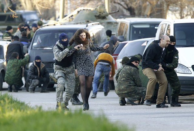 Civilians are led by members of pro-Russian self-defence units as they run outside a military base during an assault in the Crimean town of Belbek near Sevastopol March 22, 2014. Russian troops forced their way into a Ukrainian airbase in Crimea with armored vehicles, automatic fire and stun grenades on Saturday, injuring a Ukrainian serviceman and detaining the base's commander for talks. (Photo by Vasily Fedosenko/Reuters)