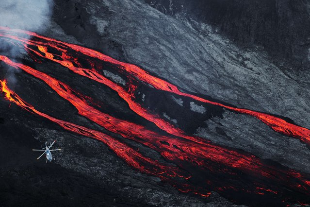 A helicopter flies overhead as lava flows out of the Piton de la Fournaise volcano as it erupts on May 17, 2015 on the French island of La Reunion in the Indian Ocean. The Piton de la Fournaise started to erupt early on May 17, with its last eruption dating back to February 4. (Photo by Richard Bouhet/AFP Photo)