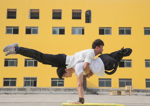 A parkour performer who has lost his legs practises new movements with his performance partner in Hefei, Anhui Province, China, in this April 7, 2016 picture. (Photo by Reuters/Stringer)