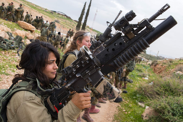 Israeli soldiers from the mixed-gender Lions of the Jordan battalion, under the Kfir Brigade, check their weapons at the end of the last training before being assigned their posting, on February 28, 2017, near the West Bank village of Bardale, east of Jenin. (Photo by Jack Guez/AFP Photo)
