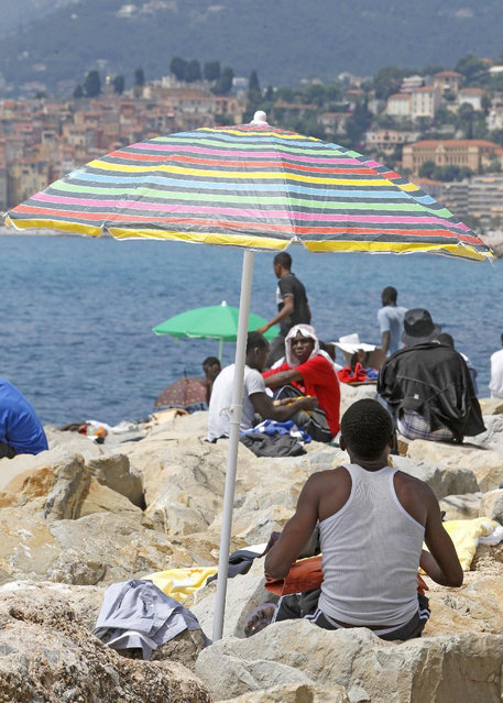 Migrants crowd on the rocky beach at the Franco-Italian border near Menton, southeastern France, Tuesday, June 16, 2015.   Italian police in riot gear forcibly removed a few dozen African migrants on Tuesday who had been camping out for days at Italy's Mediterranean border with France in hopes of going further north. (AP Photo/Lionel Cironneau)