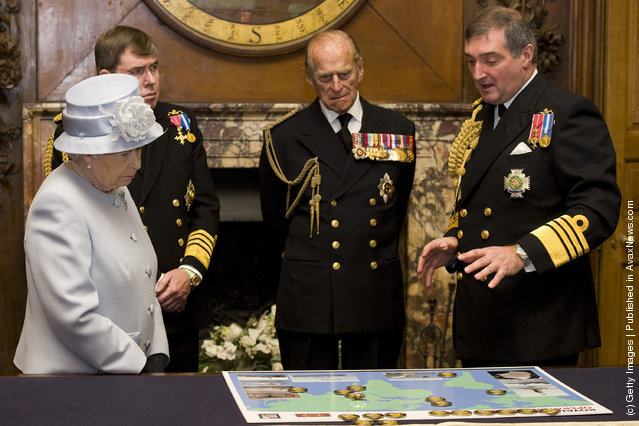 Queen Elizabeth II accompanied by First Sea Lord, Admiral Sir Mark Stanhope (2L) and her husband Prince Philip, Duke of Edinburgh, are shown a map detailing current naval deployments by Admiral Sir Trevor Soar (R) during a visit to the Admiralty Board and Admiralty House