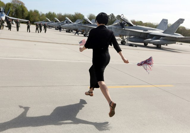 "Christy Brugger runs to greet her husband, Lt. Mike Brugger, as the ""Ragin' Bulls"" of VFA-37 return to Oceana Naval Air Station in Virginia Beach, Va., April 17, 2014. Deployed as part of Harry S. Truman Carrier Strike Group, the squadron participated in Operation Enduring Freedom and several multinational exercises in support of maritime security operations. (Photo by Steve Earley/AP Photo/The Virginian-Pilot)"