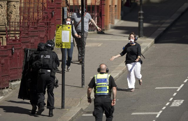 During a training exercise for London's emergency services, people run towards armed police officers as they emerge from the disused Aldwych underground train station in London, Tuesday, June 30, 2015. (Photo by Matt Dunham/AP Photo)