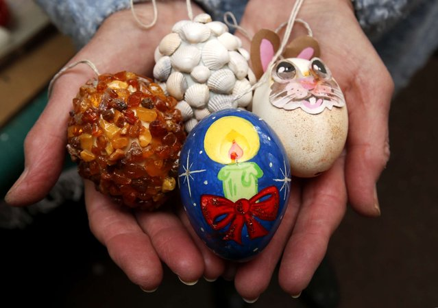 German pensioner Christa Kraft displays a selection of colourful hand-painted Easter eggs before decorating an apple tree with them, in the garden of her summerhouse in the eastern German town of Saalfeld, March 19, 2014. (Photo by Fabrizio Bensch/Reuters)