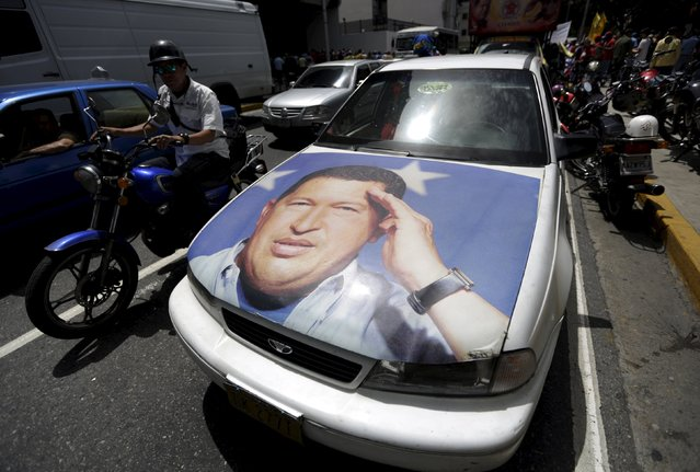 A car with the image of Venezuela's late President Hugo Chavez are see before a demonstration of union members of Empresas Polar's beer factory in Caracas, July 2, 2015. (Photo by Jorge Dan Lopez/Reuters)