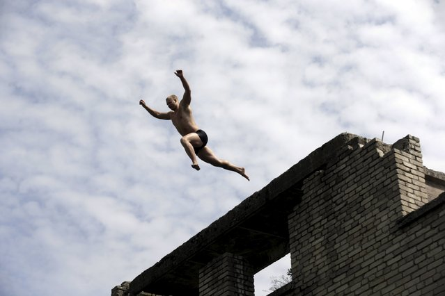A man jumps into water from the roof of Murru prison, an abandoned Soviet prison, in Rummu quarry, Estonia, during hot weather July 4, 2015. (Photo by Ints Kalnins/Reuters)