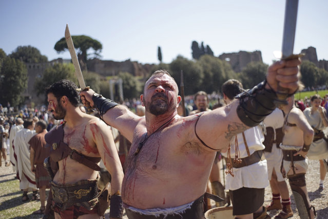 A performer dressed in traditional ancient Roman costume prepares to parade along the ancient Roman ruins of the Colosseum, Circus Maximus and the Roman Forum to celebrate the festivities of the Christmas of Rome, at Circus Maximus, Monday, April 21, 2014. Legend says that Rome was founded by Romulus on April 21, 753 BC in an area surrounded by seven hills. (Photo by Andrew Medichini/AP Photo)