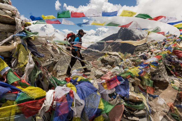 On the trek to Mount Everest, Mingma Ongel Sherpa passes by prayer flags at a memorial for Sherpas who died on the peak. Since the first expeditions in the 1920s, 99 Sherpas and other Nepalis have been killed on Everest – about 40 percent of all climbing deaths there. (Photo by Aaron Huey/National Geographic)