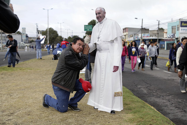 A man poses for a photo with a life size cutout of Pope Francis at Bicentennial Park where the pontiff celebrated Mass for an estimated half-million people, in Quito, Ecuador, Tuesday, July 7, 2015. (Photo by Ana Buitron/AP Photo)