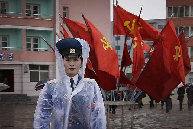 A North Korean traffic police woman directs vehicles at a street junction while behind her the sidewalk is decorated with flags of the ruling party, the Workers' Party on Thursday, May 5, 2016, in Pyongyang, North Korea. (Photo by Wong Maye-E/AP Photo)