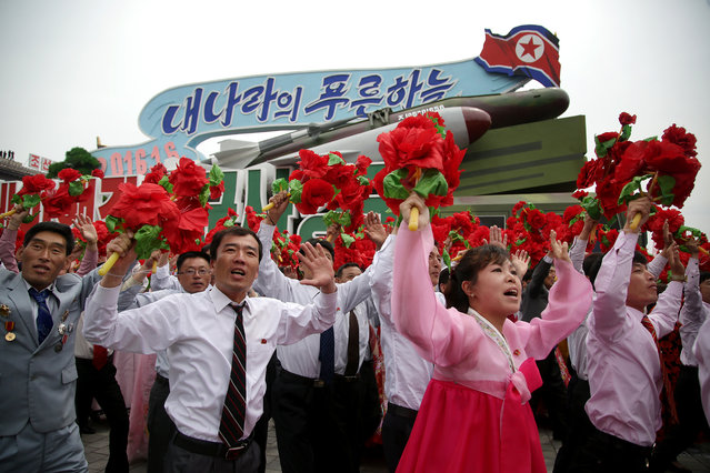 North Korean parade participants wave decorative bouquets of flowers and carry their country's national flag as they march with different types of models of missiles at the Kim Il Sung Square on Tuesday, May 10, 2016, in Pyongyang, North Korea. (Photo by Wong Maye-E/AP Photo)