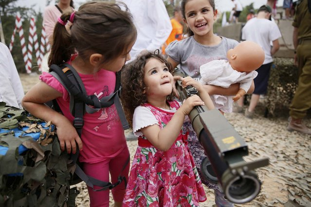 An Israeli child holds a rocket launcher as another holds her doll during a traditional military weapon display to mark the 66th anniversary of Israel's Independence at the West Bank settlement of Efrat on May 6, 2014 near the biblical city of Bethlehem. Israelis are marking Independence Day, celebrating the 66th year since the founding of the Jewish State in 1948 according to the Jewish calendar. (Photo by Gali Tibbon/AFP Photo)
