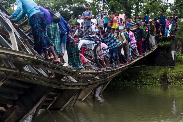 Bangladeshi pedestrian cross a broken baily brideg on July 7, 2019 in Sylhet. Heavy vehicle movement was restricted in this bridge but when a cement bag loaded truck got into the bridge, Suddenly, it collapse. (Photo by AFP Photo/Stringer)