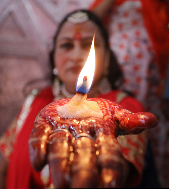 An Indian woman offers prayers at a historical Hindu Chamunda Devi temple on the first day of the nine-day long Navratri festival in Kangra,Himachal Pradesh, India, 27 September 2019. Celebrated twice a year during the spring and the fall seasons, the nine-day long Navratri festival is dedicated to the Hindu Goddess Durga. (Photo by Sanjay Baid/EPA/EFE)