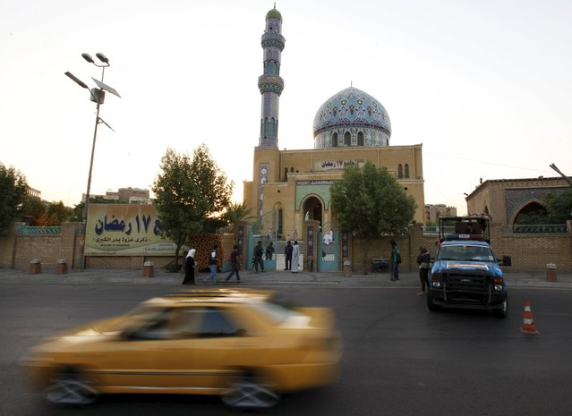 A car drives past a Sunni mosque at al-Firdous Square in Baghdad, July 17, 2015. (Photo by Ahmed Saad/Reuters)