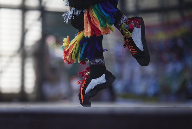 "A ""scissors"" dancer performs in a national scissors dance competition at Lima's Exposition Park, May 18, 2014. The Danza de las tijeras, or scissors dance, is a traditional dance from the Peruvian southern region of the Andes, in which two or more performers take turns dancing while accompanied with music from a harp and a violin. Dancers would display various skills and moves, which include cutting the air with the use of a scissors. (Photo by Enrique Castro-Mendivil/Reuters)"