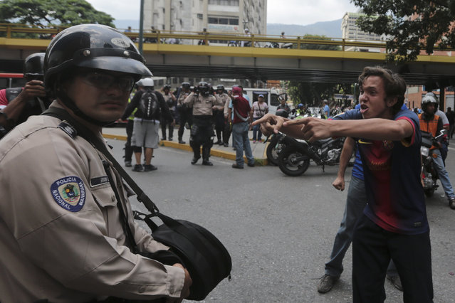 An anti-government protester shouts at a police officer in downtown Caracas, Venezuela, Wednesday, May 10, 2017. (Photo by Fernando Llano/AP Photo)