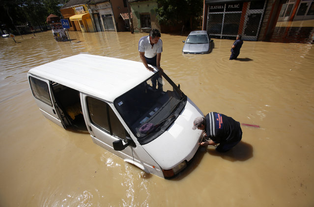 Two men trying to restart their van stuck in a flooded street in Obrenovac, some 30 kilometers (18 miles) southwest of Belgrade, Serbia, Monday, May 19, 2014. Belgrade braced for a river surge Monday that threatened to inundate Serbia's main power plant and cause major power cuts in the crisis-stricken country as the Balkans struggle with the consequences of the worst flooding in southeastern Europe in more than a century. (Photo by Darko Vojinovic/AP Photo)