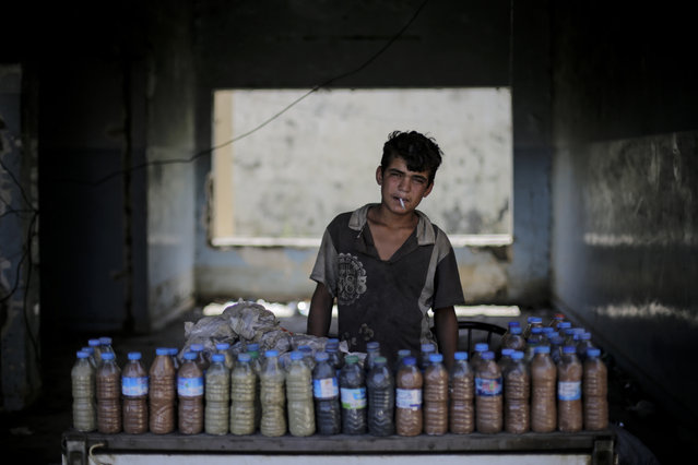 Abdul Aziz, 15, smokes a cigarette while waiting for customers to buy the mud from a sulphur well near the Hamam Alil spa south of Mosul, Iraq on Thursday, April 27, 2017. The mud is supposedly healthy for the skin. Before the Islamic State took over the town of Hamam Alil in 2014, people from all over Iraq visited the historic spa. (Photo by Bram Janssen/AP Photo)