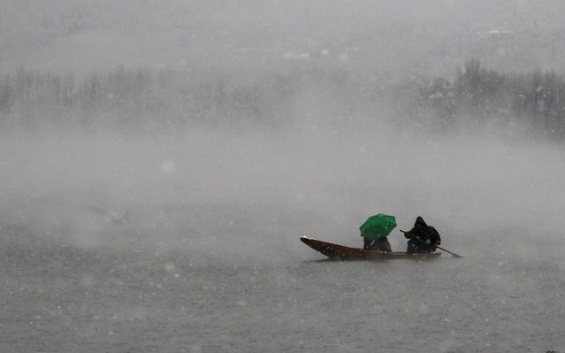 A man rows a boat on the Dal Lake as another holds an umbrella during the season's first snowfall in Srinagar November 7, 2019. (Photo by Danish Ismail/Reuters)