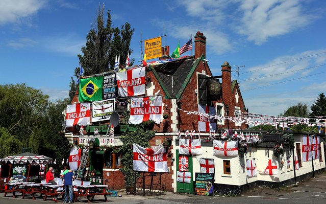 Decorations and flags cover the outside of The Robin Hood public house, in Jarrow, England, June 9, 2014. (Photo by Scott Heppell/Associated Press)