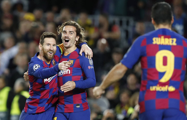 Barcelona's Lionel Messi, left, celebrates after scoring his side's second goal with Antoine Griezmann, centre and Luis Suarez during a Champions League soccer match Group F between Barcelona and Dortmund at the Camp Nou stadium in Barcelona, Spain, Wednesday, November 27, 2019. (Photo by Joan Monfort/AP Photo)