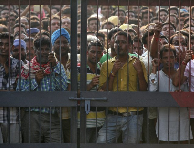 Onlookers stand at the gate of a police station where a gunfight took place inDinanagar town in Gurdaspur district of Punjab, India, July 27, 2015. (Photo by Mukesh Gupta/Reuters)