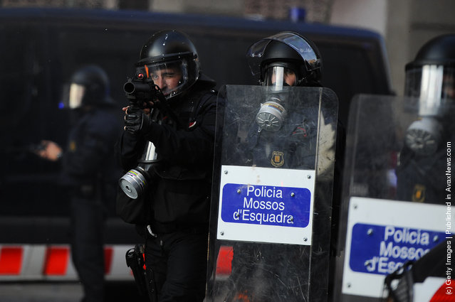 Riot police aims his gun towards demonstrators during heavy clashes with demonstrators during a 24-hour strike on March 29, 2012 in Barcelona, Spain