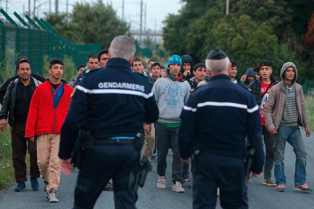 Police officers block migrants along a road to prevent their access to train tracks which lead to the Channel Tunnel, in Calais, northern France, Wednesday, July 29, 2015. Migrants rushed the tunnel linking France and England repeatedly for a second night on Wednesday and one man was crushed by a truck in the chaos, deepening tensions surrounding the thousands of people camped in this northern French port city. (Photo by Thibault Camus/AP Photo)