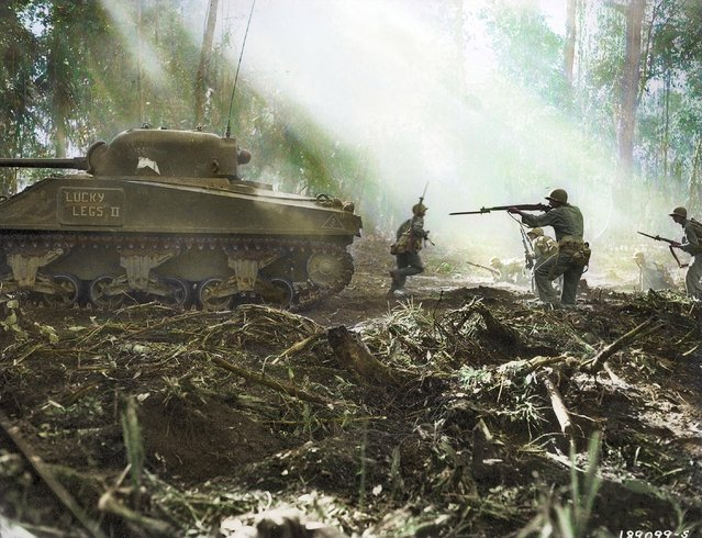 U.S. Army soldiers on Bougainville, an island in Papua New Guinea, taking cover behind an M4 Sherman tank, February 1943. (Photo by Royston Leonard/Mediadrumworld)