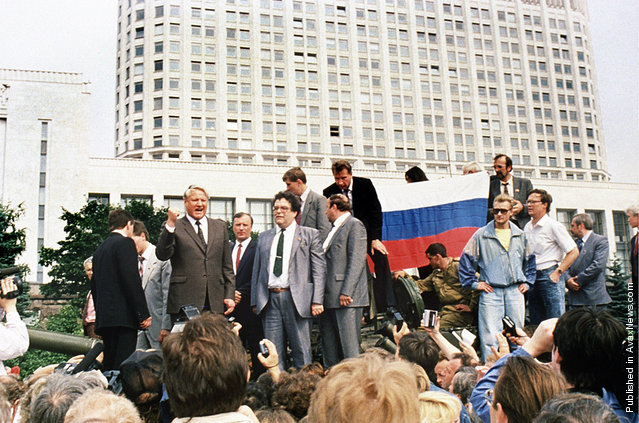 Russian President Boris Yeltsin (left) stands on top of an armored vehicle parked in front of the Russian Federation building as supporters hold a Russian federation flag on August 19, 1991, during a coup attempt. Yeltsin addressed a crowd of supporters calling for a general strike