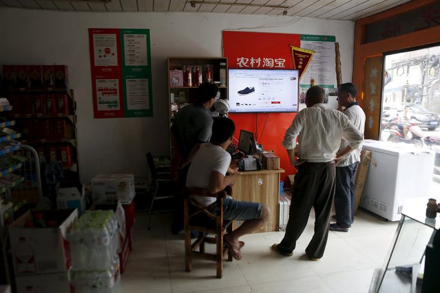Villagers look at a screen displaying a website of Alibaba's Taobao at a rural service centre in Yuzhao Village, Tonglu, Zhejiang province, China, July 20, 2015. (Photo by Aly Song/Reuters)