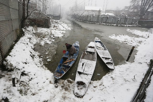 A woman cleans her boat after a snowfall in Srinagar, December 13, 2019. (Photo by Danish Ismail/Reuters)