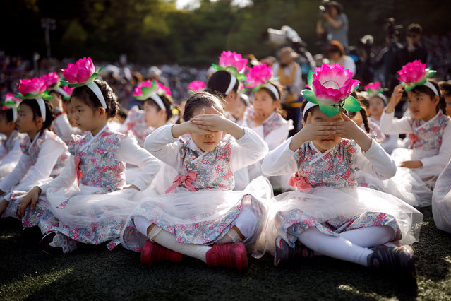 Children wearing a lantern headband rest before a Lotus Lantern parade in celebration of the upcoming birthday of Buddha in Seoul, South Korea on April 29, 2017. (Photo by Kim Hong-Ji/Reuters)