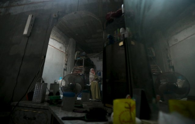 A Palestinian woman is reflected in a mirror as she stands inside her house during power cut at Shatti (beach) refugee camp in Gaza City July 23, 2015. (Photo by Mohammed Salem/Reuters)
