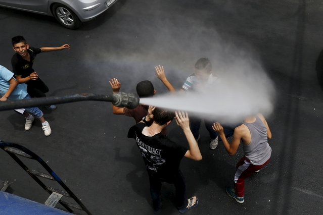 Children react as Greater Amman Municipality personnel spray them with a water sprinkler in order to cool them down as part of measures to ease the effect of a heatwave, in Amman, Jordan, August 3, 2015. (Photo by Muhammad Hamed/Reuters)