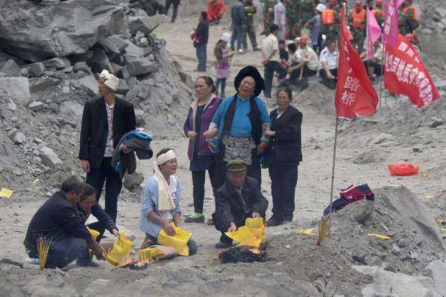 Relatives burn incense and paper offerings to appease the dead at the site of a landslide in Xinmo village in Maoxian County in southwestern China's Sichuan Province, Sunday, June 25, 2017. (Photo by Ng Han Guan/AP Photo)