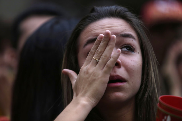A Brazilian soccer fan cries as she watches her team get beat during a live telecast of the semi-finals World Cup soccer match between Brazil and Germany, in Belo Horizonte, Brazil, Tuesday, July 08, 2014. (Photo by Bruno Magalhaes/AP Photo)