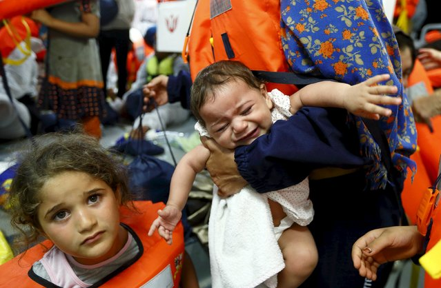 Migrant children on the Migrant Offshore Aid Station (MOAS) ship MV Phoenix wait to be transferred to the Norwegian ship Siem Pilot off the coast of Libya August 6, 2015. An estimated 700 migrants on an overloaded wooden boat were rescued 10.5 miles (16 kilometres) off the coast of Libya by the international non-governmental organisations Medecins san Frontiere (MSF) and MOAS without loss of life on Thursday afternoon. (Photo by Darrin Zammit Lupi/Reuters)